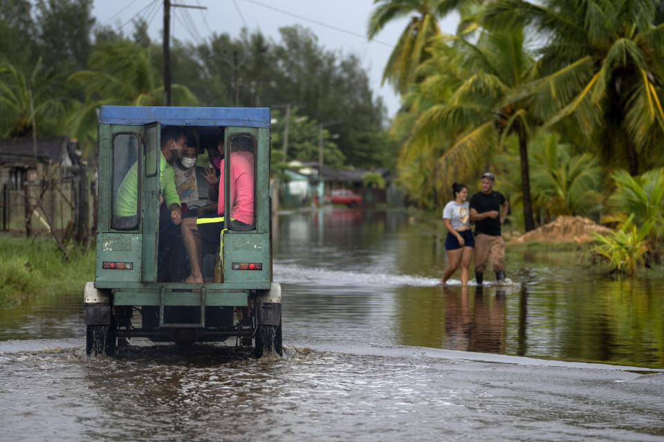 Passengers sit in the back of a vehicle as they are transported through a street flooded by rain brought on by Hurricane Ida, in Guanimar, Artemisa province, Cuba, Saturday Aug. 28, 2021. (AP Photo/Ramon Espinosa)