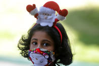 A Sri Lankan Christian girl wears a Santa hair band and a face mask as a precaution against the coronavirus as she arrives at a church to attend the Christmas mass in Colombo, Sri Lanka, Friday, Dec. 25, 2020. (AP Photo/Eranga Jayawardena)