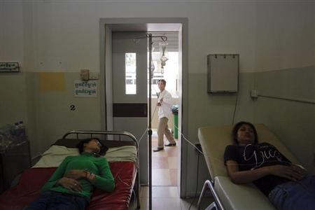 Garment workers recover at a hospital after fainting at a factory in Phnom Penh