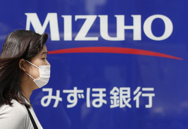 A woman walks past a branch of Mizuho bank, belonging to Mizuho Financial Group, in Tokyo