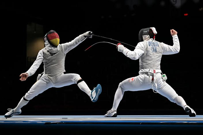 <p>Germany's Andre Sanita (L) compete against Canada's Blake Broszus in the mens team foil qualifying bout during the Tokyo 2020 Olympic Games at the Makuhari Messe Hall in Chiba City, Chiba Prefecture, Japan, on August 1, 2021. (Photo by Fabrice COFFRINI / AFP)</p>