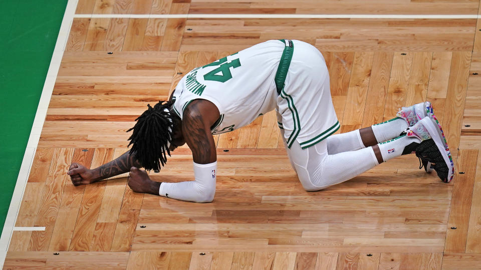 Boston Celtics center Robert Williams III pounds the floor following an apparent injury, after rebounding a shot by Washington Wizards guard Russell Westbrook during the first half of an NBA basketball Eastern Conference play-in game Tuesday, May 18, 2021, in Boston. Williams was escorted to the locker room by medical staff after the incident. (AP Photo/Charles Krupa)