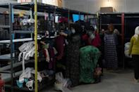 Women look at donated clothes inside the Ritsona camp for refugees and migrants