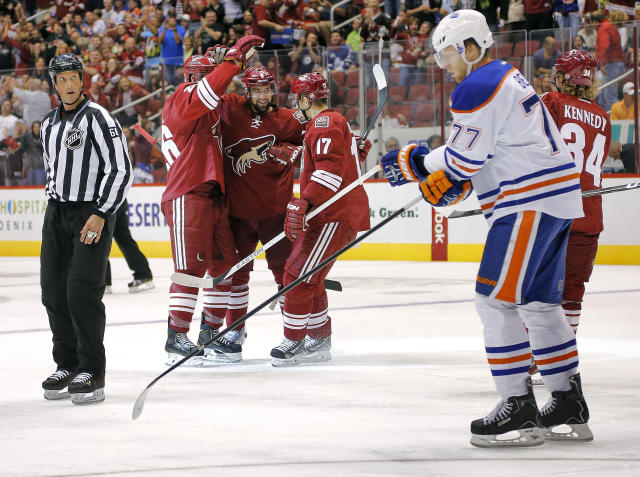 Phoenix Coyotes' David Schlemko, center, celebrates his goal with teammates Radim Vrbata (17) and Michael Stone, left, as Edmonton Oilers' Anton Belov (77), of Russia, skates by during the second period of an NHL hockey game Saturday, Oct. 26, 2013, in Glendale, Ariz. (AP Photo/Matt York)