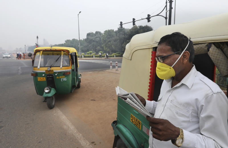 A three wheeler driver waits for passengers at a crossing wearing a pollution mask in New Delhi, India, Thursday, Nov. 7, 2019. The air quality index stood at 273 on Thursday in the capital after authorities declared a health emergency last weekend when the index crossed 500 — 10 times the level considered healthy by WHO standards. (AP Photo/Manish Swarup)