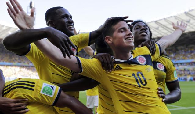 In this Saturday, June 14, 2014 photo, Colombia's James Rodriguez, front, center right, celebrates with his teammates after scoring his side's third goal during the group C World Cup soccer match against Greece at the Mineirao Stadium in Belo Horizonte, Brazil. Colombia defeated Greece 3-0. (AP Photo/Fernando Vergara)