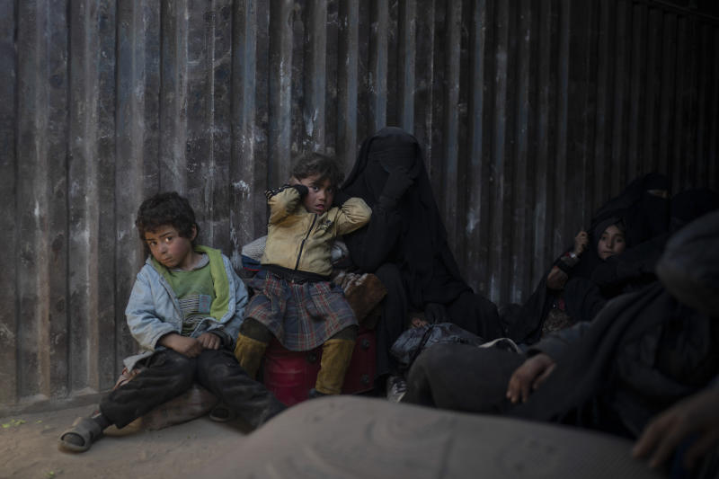 Women and children ride in the back of a truck that is part of a convoy evacuating hundreds out of the last territory held by Islamic State militants in Baghouz, eastern Syria, Wednesday, Feb. 20, 2019. The evacuation signals the end of a week long standoff and opens the way to U.S.-backed Syrian Democratic Forces (SDF) recapture the territory. (AP Photo/Felipe Dana)