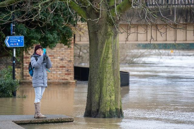 A woman takes a photo of flooding in Bedford