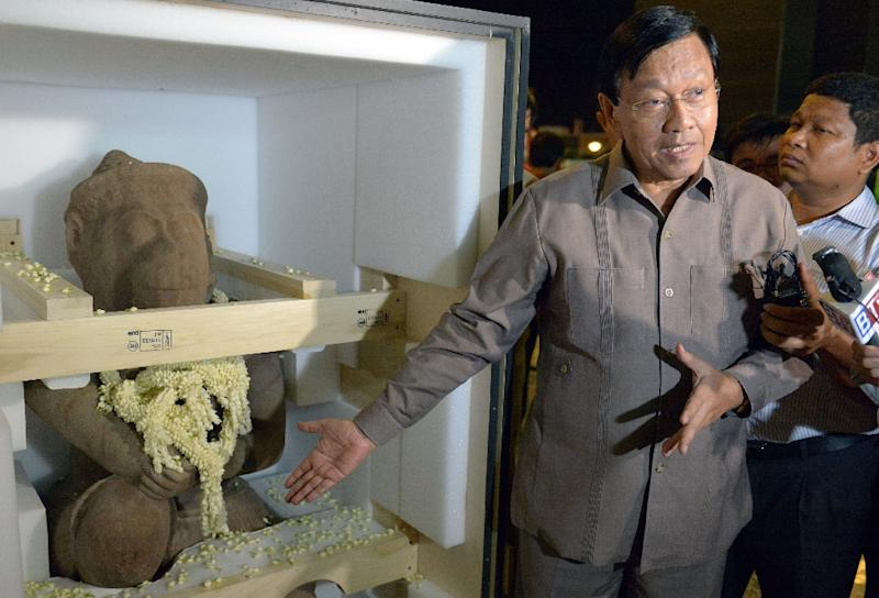 Cambodian official Chan Tani stands next to a 10th-century sandstone statue of the Hindu monkey god Hanuman upon its return to Cambodia from the US on May 10, 2015 (AFP Photo/Tang Chhin Sothy)