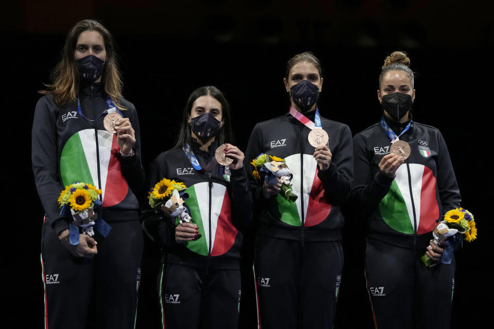 Bronze medalists from Italy celebrate on the podium of the women's Foil team final at the 2020 Summer Olympics, Thursday, July 29, 2021, in Chiba, Japan. (AP Photo/Hassan Ammar)