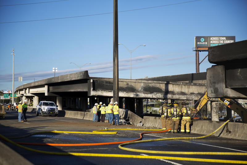 Construction workers and firefighters survey a section of an overpass that collapsed from a large fire on Interstate 85 in Atlanta, Friday, March 31, 2017. Many commuters in some of Atlanta's densely populated northern suburbs will have to find alternate routes or ride public transit for the foreseeable future after a massive fire caused a bridge on Interstate 85 to collapse Thursday, completely shutting down the heavily traveled highway. (AP Photo/David Goldman)