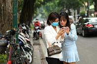 Insurance saleswoman Nguyen Thi Thanh Loan (R) checks her mobile phone after getting her photographs taken by a friend in Hanoi, a day after taking the course