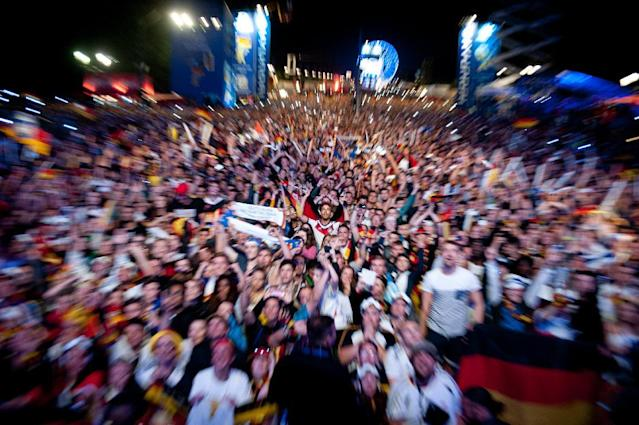 In this zoomed picture, German soccer fans react after Germany won the final match of the Brazil World Cup 2014 between Germany and Argentina played in Rio de Janeiro, Brazil, at a public viewing area called 'Fan Mile' in Berlin, Sunday, July 13, 2014. Germany won by 1-0. (AP Photo/Steffi Loos)