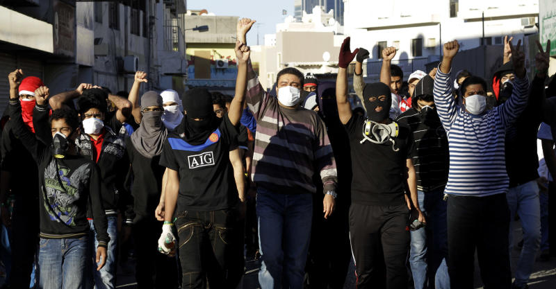 Bahraini anti-government protesters chant slogans during clashes with riot police in Sanabis, Bahrain, Thursday, Feb. 14, 2013. Security forces in Bahrain clashed on Thursday with anti-government protesters in street battles that left at least one boy dead amid high tensions on the second anniversary of the uprising in the Gulf nation, activists said. (AP Photo/Hasan Jamali)