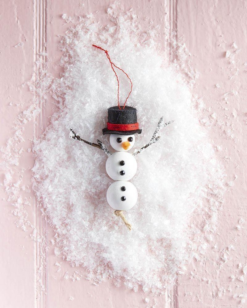"""<p>We promise this sweet DIY Frosty won't melt while he hangs on your tree this holiday season.</p><p><strong>To make:</strong> Paint three wooden craft beads with white acrylic paint. When dry thread a piece twine through the holes of the beads and knot to hold together. Attach two black gem mini crystal rhinestones for the eyes and four for the buttons with hot glue. Snip a short lengths of orange felt and attach just below the eyes with hot glue. Attach stick arms to the side of the middle bead with hot glue. Flock arms, if desired. Wrap a thin length of red felt to a <a href=""""https://www.amazon.com/Pengxiaomei-Plastic-Miniature-Crafts-Supplies/dp/B082X3B6XD/ref=sr_1_2?tag=syn-yahoo-20&ascsubtag=%5Bartid%7C10050.g.1070%5Bsrc%7Cyahoo-us"""" rel=""""nofollow noopener"""" target=""""_blank"""" data-ylk=""""slk:mini black top hat"""" class=""""link rapid-noclick-resp"""">mini black top hat</a> with hot glue. Glue a string to the top of the hat for hanging. Glue hat to snowman's head.</p><p><a class=""""link rapid-noclick-resp"""" href=""""https://www.amazon.com/TecUnite-Crystal-Rhinestones-Tweezer-Picking/dp/B07FF3GKMN/ref=sr_1_2_sspa?tag=syn-yahoo-20&ascsubtag=%5Bartid%7C10050.g.1070%5Bsrc%7Cyahoo-us"""" rel=""""nofollow noopener"""" target=""""_blank"""" data-ylk=""""slk:SHOP BLACK GEM MINI CRYSTAL RHINESTONES"""">SHOP BLACK GEM MINI CRYSTAL RHINESTONES</a></p>"""