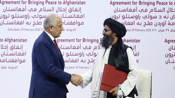 U.S. Special Representative for Afghanistan Reconciliation Zalmay Khalilzad (L) and Taliban co-founder Mullah Abdul Ghani Baradar (R) shake hands after signing the peace agreement between US, Taliban, in Doha, Qatar on February 29, 2020. (Fatih Aktas/Anadolu Agency via Getty Images)