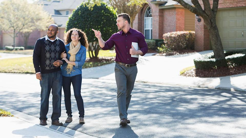 An African American couple walking on a residential street, with a young man holding a folder.