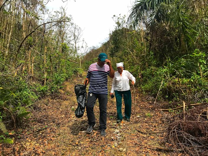 Jesse Vazquez and his mother, Mercedes Mercado, hike along a muddy path to their farm in Hatillo, Puerto Rico, on Oct. 10, 2017, to survey the damage from Hurricane Maria. (Photo: Caitlin Dickson/Yahoo News)