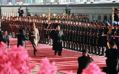 North Korean leader Kim Jong-un inspects a guard of honour before boarding the train at Pyongyang Station - Credit: AFP