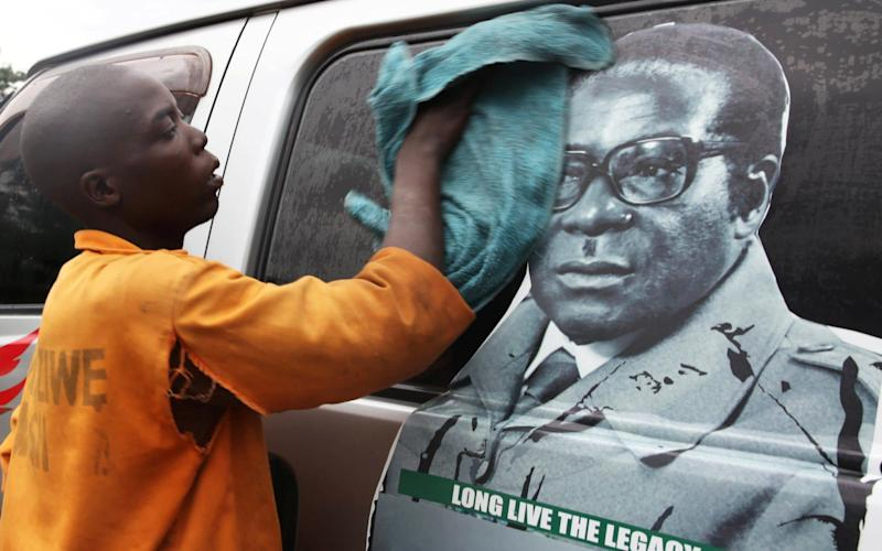 A young man in Harare washes a minibus adorned with picture of President Robert Mugabe - REUTERS
