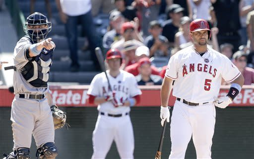 New York Yankees catcher Chris Stewart, left, gestures after Los Angeles Angels' Albert Pujols, right, struck out with the bases loaded to end a baseball game in Anaheim, Calif., Sunday, June 16, 2013. (AP Photo/Chris Carlson)