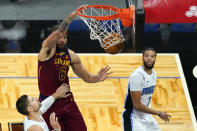 Cleveland Cavaliers center JaVale McGee (6) dunks the ball over Orlando Magic center Nikola Vucevic, left, and guard Michael Carter-Williams, right, during the first half of an NBA basketball game, Monday, Jan. 4, 2021, in Orlando, Fla. (AP Photo/John Raoux)