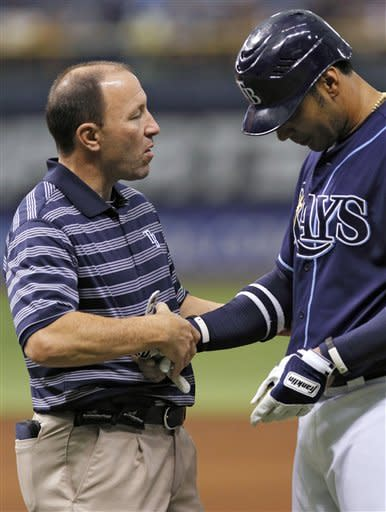 Tampa Bay Rays trainer Ron Porterfield, left, checks on Carlos Pena after he was hit with a pitch by Toronto Blue Jays starting pitcher Ricky Romero during the third inning of a baseball game, Wednesday, May 23, 2012, in St. Petersburg, Fla. Pena remained in the game. (AP Photo/Chris O'Meara)