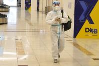 A passenger in a full, disposable hazmat suit arrives at the baggage claim area of Dubai International Airport's Terminal 3 in Dubai, United Arab Emirates, Thursday, Nov. 26, 2020. The low-cost carrier flyDubai began regular flights to Tel Aviv on Thursday, the latest sign of the normalization deal between the UAE and Israel. (AP Photo/Jon Gambrell)