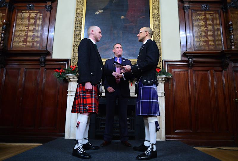 GLASGOW, SCOTLAND - DECEMBER 31: A couple of the same sex Joe Schofield (blue kilt) and Malcolm Brown from Tullibody, Clackmannanshire are married by Ross Wright, Celebrant from Humanist Society Scotland in the Trades Hall shortly after midnight in front of friends and family in one of the first same-sex and belief category weddings in Scotland on December 31, 2014 in Glasgow, Scotland. Same-sex couples have been able to enter into 'civil partnerships' since 2005, however following a change in the law on February 4, 2014. A couple of the same sex are now eligible to marry in Scotland. Parliament's decision to grant same-sex couples an equal right to marriage has been met with opposition from religious groups. Gay marriage is already legal in England and Wales, however the Northern Ireland administration has no plans to make it law. (Photo by Mark Runnacles/Getty Images)