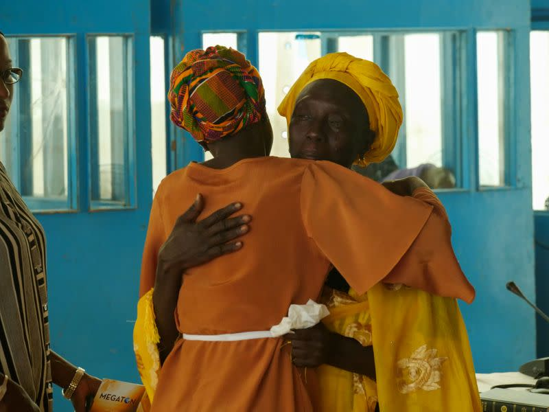 Adama Gassama, victim of the Yahya Jammeh era witch hunt, embraces a counsel after hearing at the Truth and Reconciliation and Repsarations Commission in Eassau,