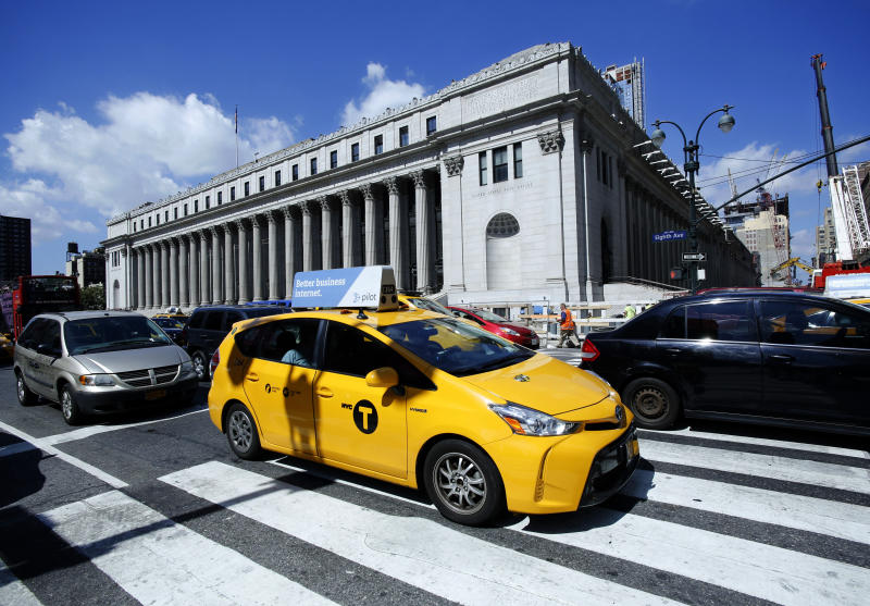 """FILE - In this Aug. 15, 2016 file photo, a taxi drives past the James A Farley Post Office Building in New York. The city of New York and the state of California sued the U.S. Postal Service Tuesday, Oct. 22, 2019,  to stop tens of thousands of cigarette packages from being mailed from foreign countries to U.S. residents, saying the smugglers are engaging in """"cigarette tax evasion"""" while postal workers look the other way. (AP Photo/Mark Lennihan, File)"""