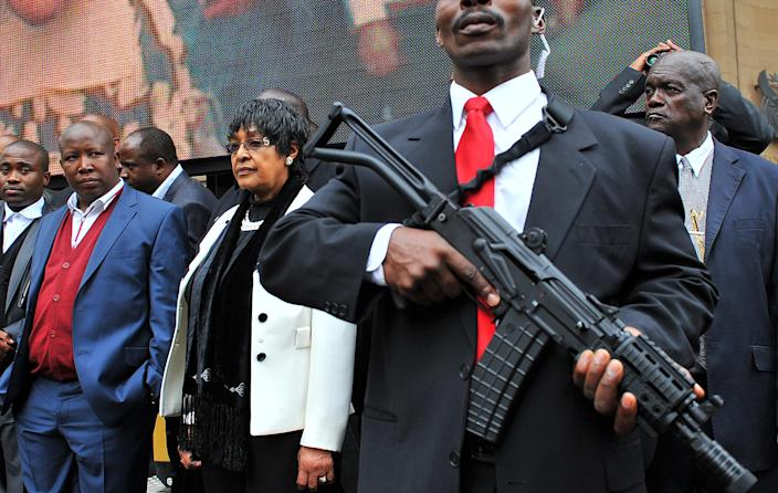 "<p>The youth leader of South Africa's ruling party, Julius Malema, second from left, and former wife of South African icon Nelson Mandela, Winnie Madikizela-Mandela, stand next to an armed bodyguard, outside the court in Johannesburg on April 21, 2011. Malema said that singing ""Shoot the Farmer"" does not incite violence during a hate speech trial that has captivated the nation. Afriforum, a lobby that sees itself as the voice of white Afrikaners, wants the song banned as hate speech in its suit against Malema. (Photo: Alexander Joe/AFP/Getty Images) </p>"
