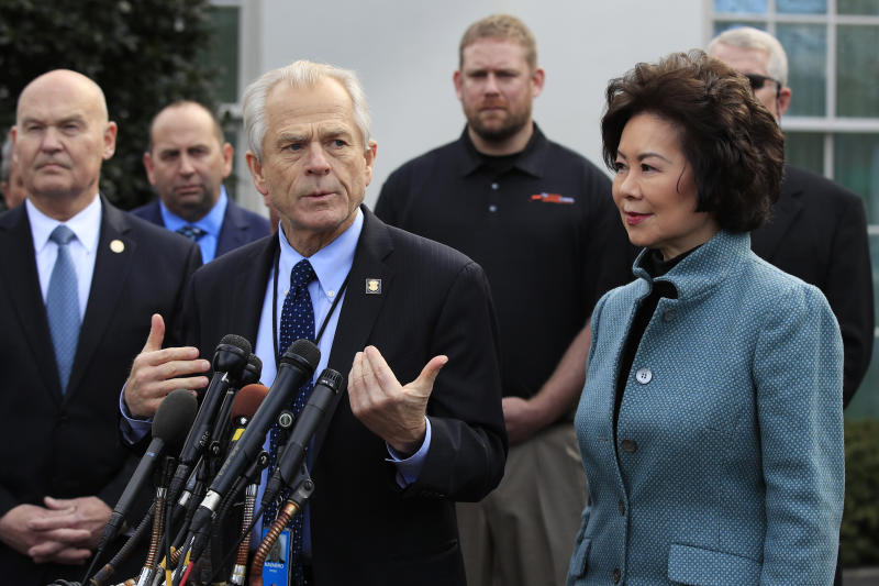 FILE - In this March 4, 2019, file photo, White House trade adviser Peter Navarro, front left, with Transportation Secretary Elaine Chao, right, and U.S. Maritime Administration Administrator Mark Buzby, back left, speaks to reporters outside the West Wing of the White House in Washington. Where past presidents have relied on top academics, business leaders and officials with experience in prior administrations, Trump has gone a different route. He's built crew of camera-ready economic advisers, rather than one known for its policy chops.  (AP Photo/Manuel Balce Ceneta, File)