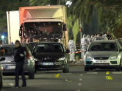 FILE - In this July 15, 2016 file photo forensic officers stand near a truck with its windscreen riddled with bullets, that plowed through a crowd of revelers who'd gathered to watch the fireworks in the French resort city of Nice, southern France. (AP Photo/Claude Paris, File)