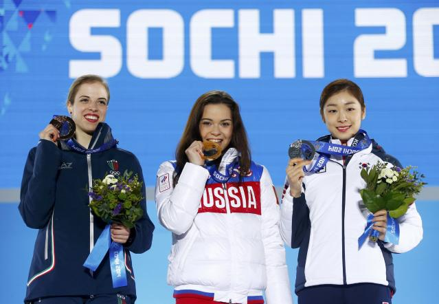Gold medallist Russia's Adelina Sotnikova (C), silver medallist South Korea's Yuna Kim (R), and bronze medallist Italy's Carolina Kostner celebrate during the victory ceremony for the figure skating women's free skating program at the 2014 Sochi Winter Olympics February 21, 2014. REUTERS/Shamil Zhumatov (RUSSIA - Tags: OLYMPICS SPORT FIGURE SKATING TPX IMAGES OF THE DAY)