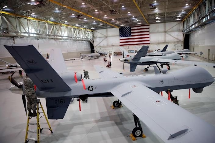 MQ-9 Reapers and an MQ-1B Predator remotely piloted aircraft (RPA) are parked in a hanger at Creech Air Force Base on November 17, 2015 in Indian Springs, Nevada. (Isaac Brekken/Getty Images)
