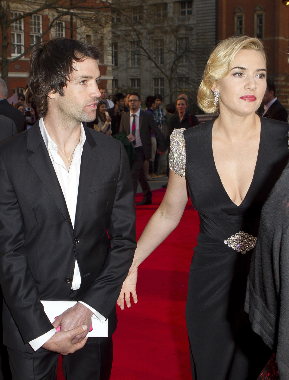 Actress Kate Winslet, right, arrives with  boyfriend Ned Rocknroll at the 'Titanic 3D' UK film premiere at the Royal Albert Hall in Kensington, West London, Tuesday, March 27, 2012. The re-launch of the Titanic 3D version comes 15 years after the film was a huge box office hit. (AP Photo/Joel Ryan)
