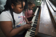 Brittani, left, and Lear Preston play the piano in their living room after their virtual school hours, Wednesday, Feb. 10, 2021, in Chicago. (AP Photo/Shafkat Anowar)