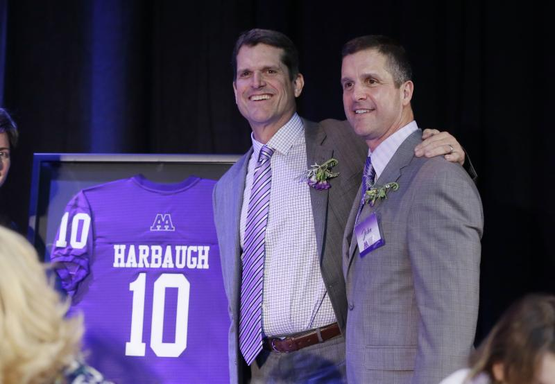 Michigan head football coach Jim Harbaugh, left, stand with his brother Baltimore Ravens head coach John Harbaugh, after his induction into the Ann Arbor Pioneer High School Hall of Fame, Friday, March 11, 2016, in Ann Arbor, Mich. (AP Photo/Carlos Osorio)