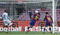 Barcelona's Lionel Messi, centre, heads the ball to score his side 1st goal of the game during the Spanish La Liga soccer match between Barcelona and Valencia at the Camp Nou stadium in Barcelona, Spain, Saturday, Dec. 19, 2020. (AP Photo/Joan Monfort)
