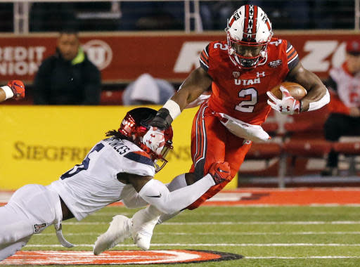 FILE- In this Oct. 12, 2018, file photo, Arizona safety Demetrius Flannigan-Fowles (6) tackles Utah running back Zack Moss (2) during the first half during an NCAA college football game, in Salt Lake City. Moss, who decided stay for his senior year rather than bolt for the NFL, has had back-to-back 1,000-yard rushing seasons.(AP Photo/Rick Bowmer, File)