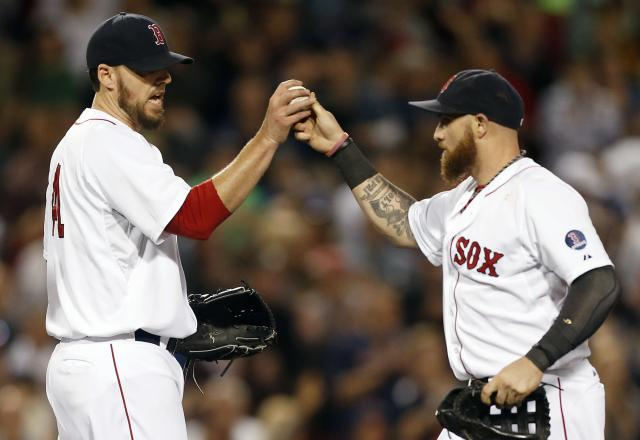 Boston Red Sox's John Lackey, left, gets the ball from Jonny Gomes after pitching nine innings and defeating the Baltimore Orioles 3-1 in a baseball game in Boston, Thursday, Sept. 19, 2013. (AP Photo/Michael Dwyer)
