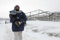 A migrant walks through the snow at the Lipa camp northwestern Bosnia, near the border with Croatia, Saturday, Dec. 26, 2020. Hundreds of migrants are stranded in a burnt-out squalid camp in Bosnia as heavy snow fell in the country and temperatures dropped during a winter spell of bad weather after fire earlier this week destroyed much of the camp near the town of Bihac that already was harshly criticized by international officials and aid groups as inadequate for housing refugees and migrants.(AP Photo/Kemal Softic)