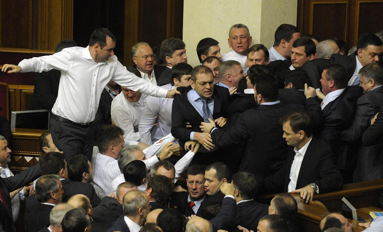 Ukrainian lawmakers fight around the rostrum during the first session of Ukraine's newly elected parliament in Kiev, Ukraine, Thursday, Dec. 13, 2012. (AP Photo/Sergei Chuzavkov)