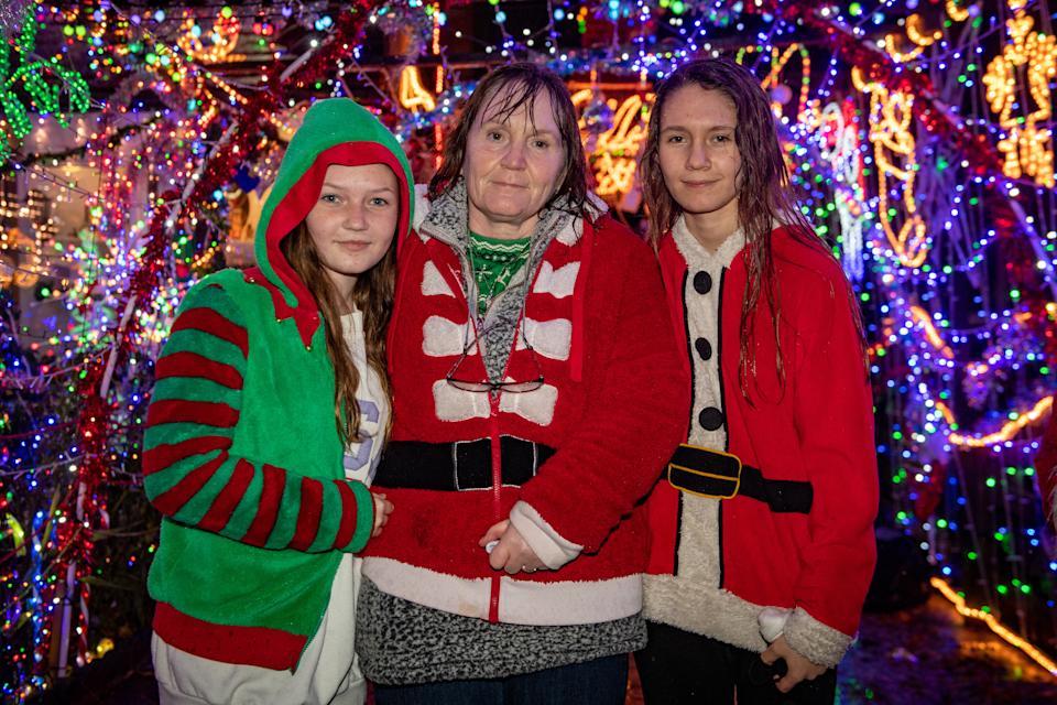 Sharon Markham, 50, turned on her dad's Christmas lights with daughters Aimee, 13 (left) and Kiara Markham, 16, after he died the previous night. (SWNS)