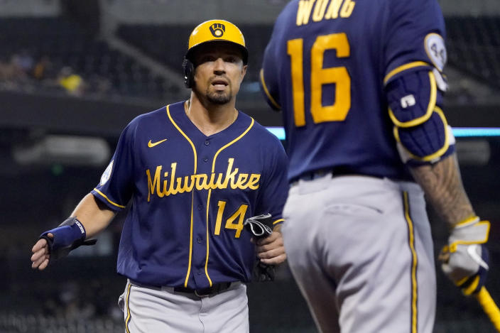 Milwaukee Brewers' Jace Peterson scores on a base hit by teammate Brandon Woodruff a he greets Kolten Wong (16) during the fifth inning of a baseball game against the Arizona Diamondbacks, Wednesday, June 23, 2021, in Phoenix. (AP Photo/Matt York)