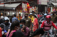 Indian policemen wearing face masks as a precautionary measure against the coronavirus walk in a market during Diwali, the Hindu festival of lights, in Jammu, India, Saturday, Nov. 14, 2020. (AP Photo/ Channi Anand)