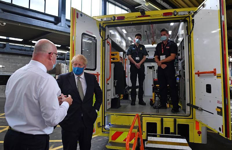 Britain's Prime Minister Boris Johnson (2L), talks with CEO London Ambulance Service Garrett Emmerson (L) after meeting brothers paramedic a paramedic Jack Binder (2R) and firefighter Tom Binder (R), standing inside the back of an ambulance, during his visit to the headquarters of the London Ambulance Service NHS Trust in central London on July 13, 2020. (Photo by Ben STANSALL / POOL / AFP) (Photo by BEN STANSALL/POOL/AFP via Getty Images)