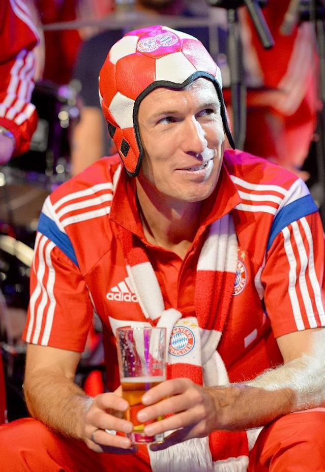 In this picture taken Saturday May 17, 2014 Bayern Munich player Arjen Robben enjoys a beer during celebrations after the team won the German soccer cup final against Borussia Dortmund, in Berlin. (AP Photo/ Stuart Franklin, Pool)