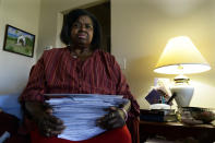 Debra Smith, 57, holds her medical bills in her living room on Thursday, Oct. 7, 2021, in Spring Hill, Tenn. Smith, who has health problems that prevent her from working, has about $10,000 in unpaid medical bills. Living expenses and prescriptions consume most of the $2,300 a month Smith gets from a pension and Social Security. (AP Photo/Mark Zaleski)